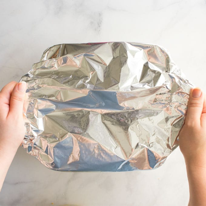 hands holding baking dish covered in foil