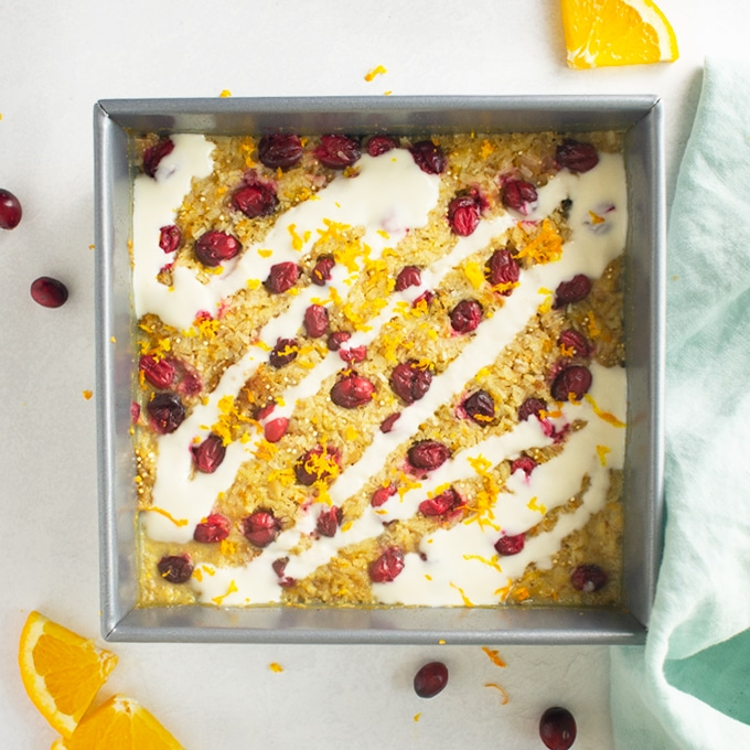quinoa breakfast bake topped with cranberries in baking dish. topped with yogurt topping.