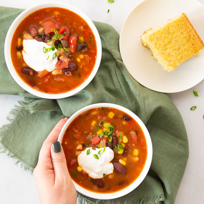 hand holding bowl of chili with a side of cornbread