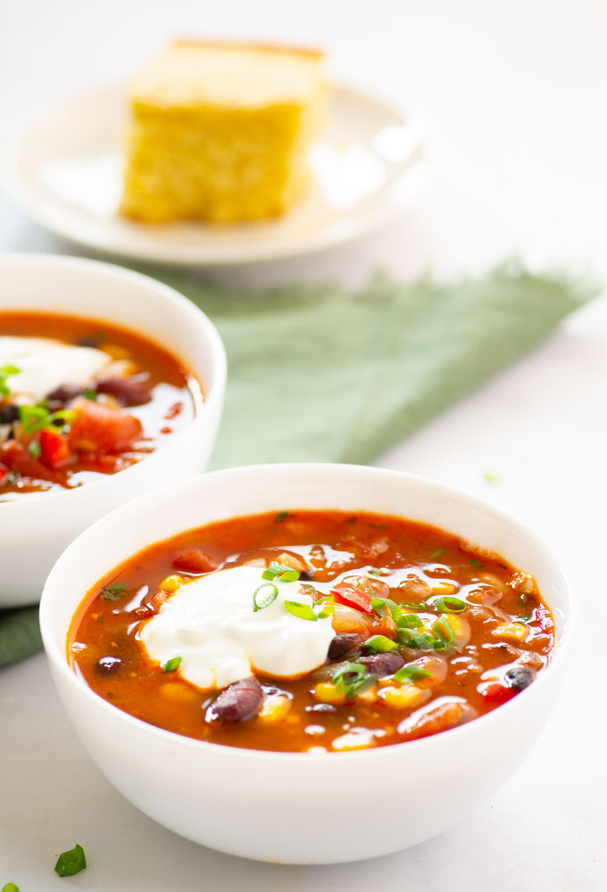 two bowls of vegan chili with cornbread in the background
