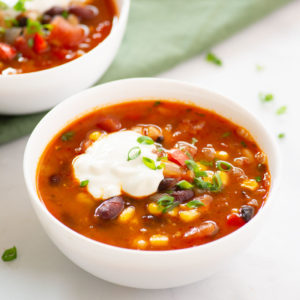 vegan chili topped with dairy-free sour cream and green onions