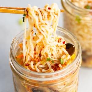 chopsticks picking up noodles out of a mason jar