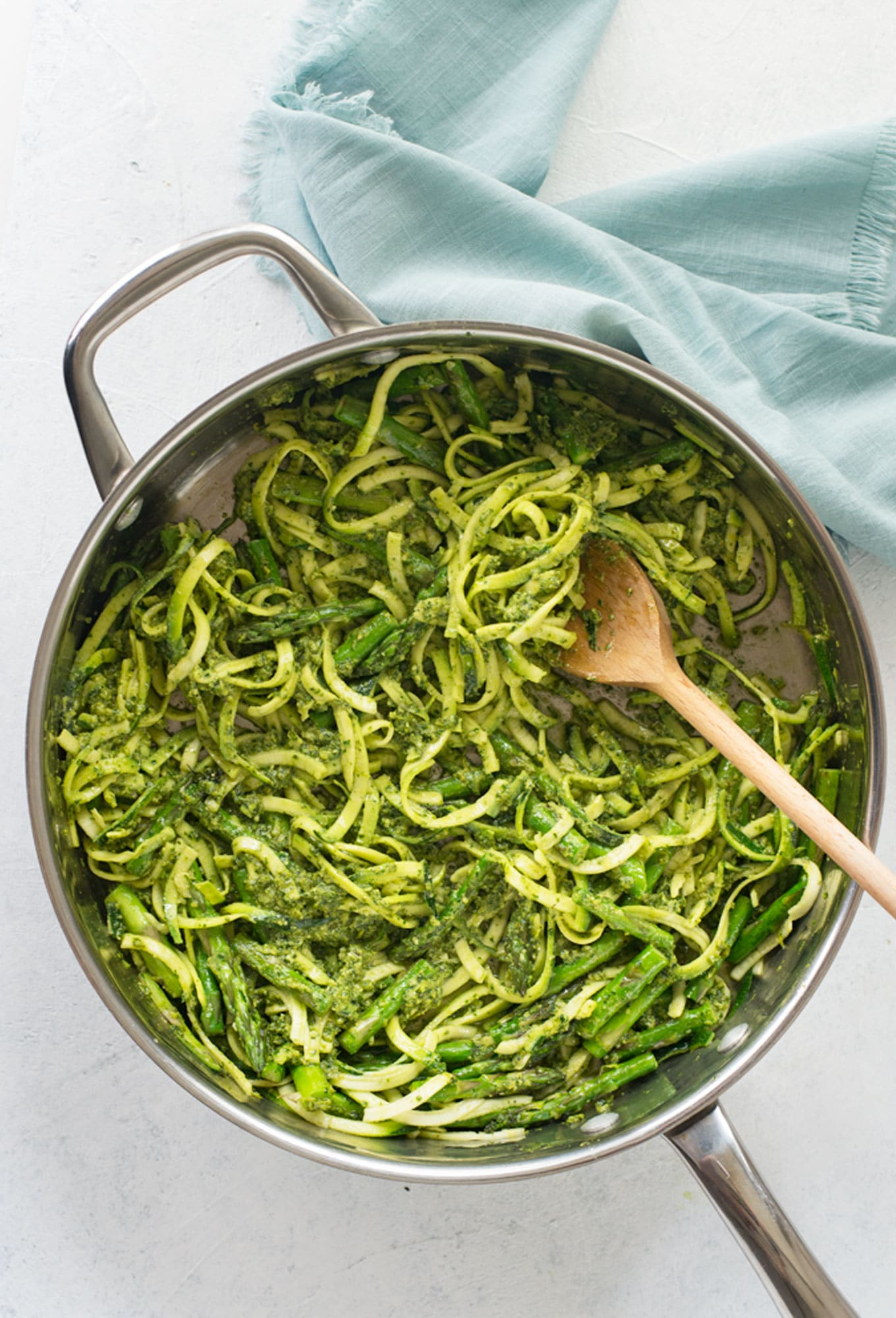 vegan one pot dinner. zoodles with lemon pesto and asparagus in pan on white background with blue napkin