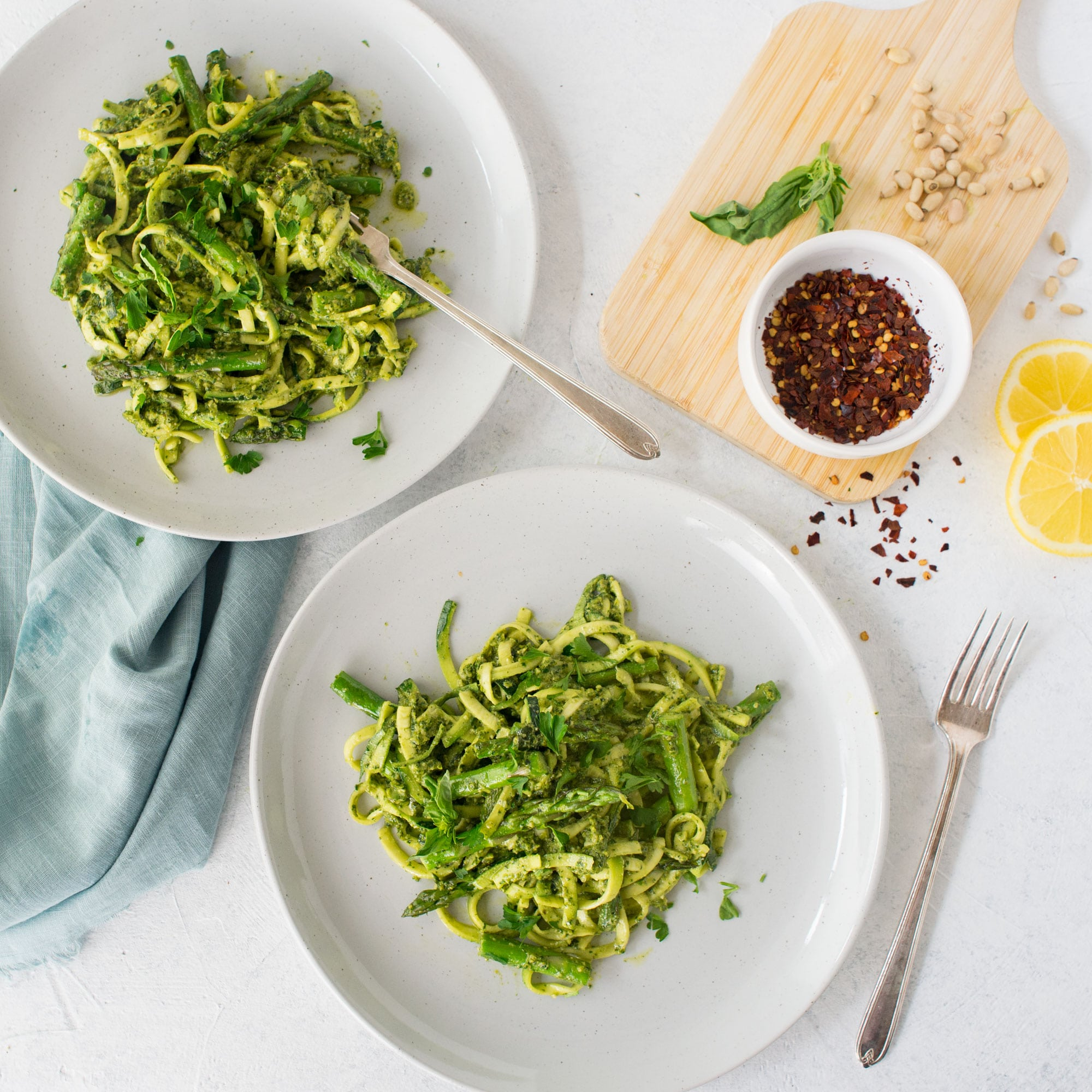 two plates of zoodles with asparagus and lemon pesto with red chili flakes, basil, and pine nuts