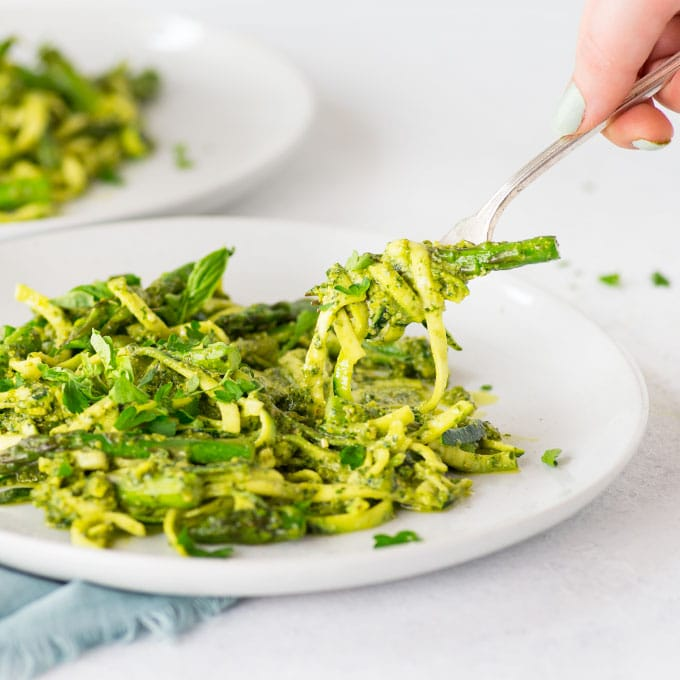 hand holding fork of zucchini noodles with asparagus and lemon pesto