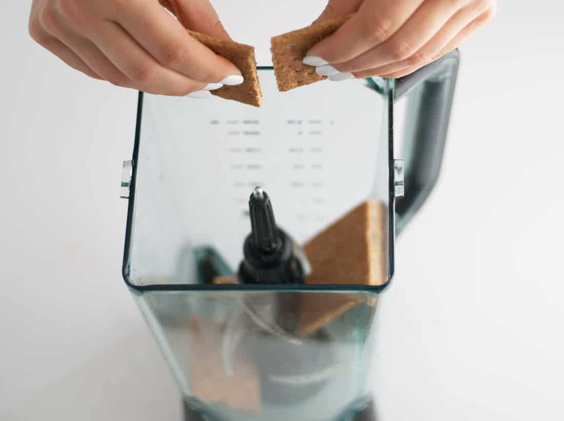 hands adding graham crackers to blender