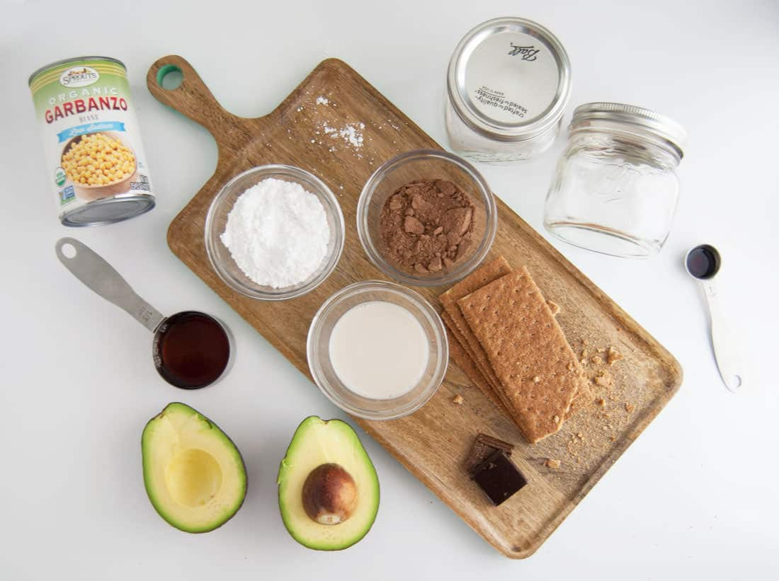 avocado, chickpeas, chocolate, graham crackers, mason jars, and almond milk on wooden board