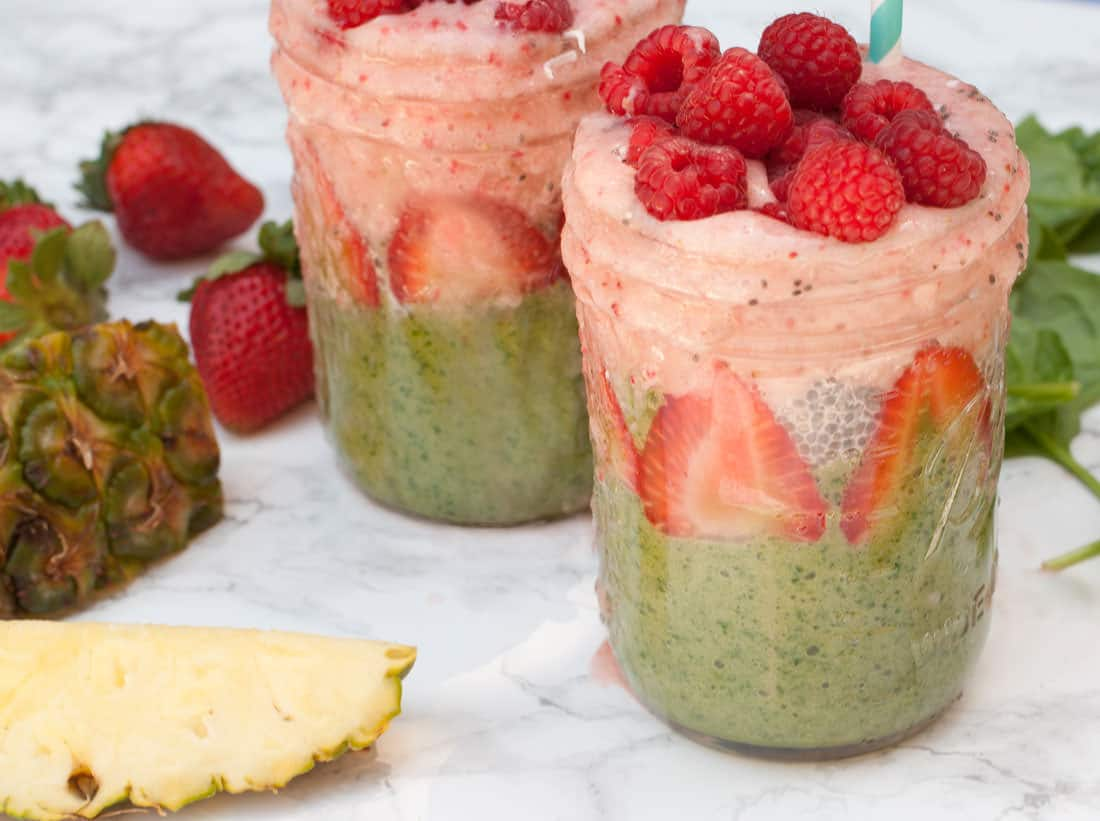 layered smoothies on marble background with pineapple and strawberry