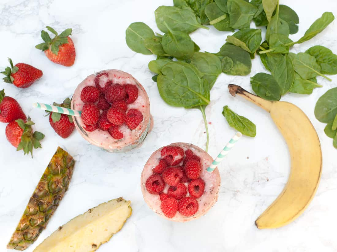 smoothies with spinach, banana, strawberries on marble background