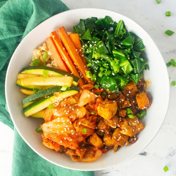 vegan bibimbap bowl topped with kimchi, sesame seeds, tofu, carrots, zucchini, and kale