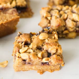 vegan peanut butter and jelly squares topped with peanuts