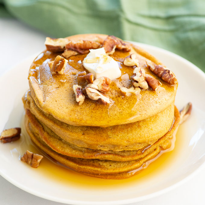 stack of vegan pumpkin pancakes with butter, maple syrup, and chopped pecans
