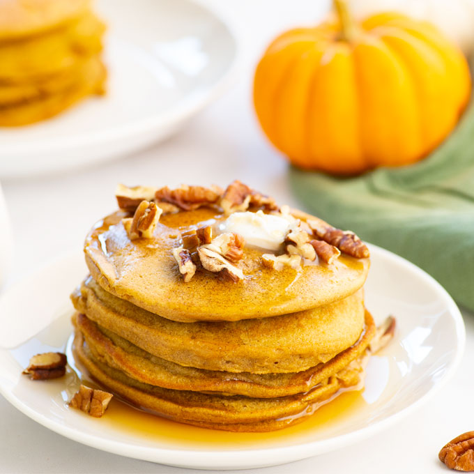 stack of vegan pumpkin pancakes topped with butter, maple syrup, and chopped pecans