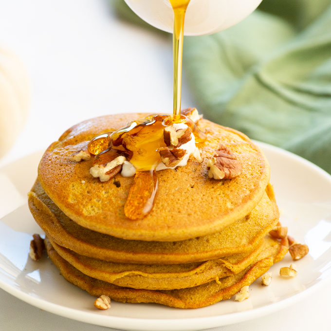 pouring maple syrup over a stack of pumpkin pancakes