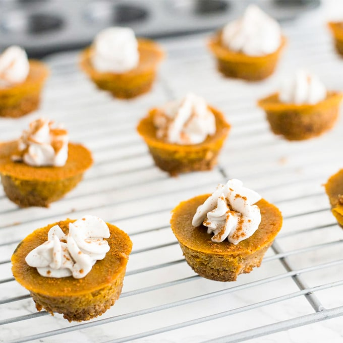 vegan mini pumpkin pie bites with chai crust on cooling rack. pumpkin pies are topped with coconut whipped cream