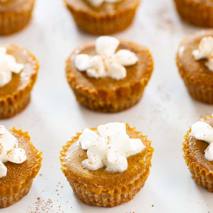 closeup of vegan mini pumpkin pies topped with whipped cream