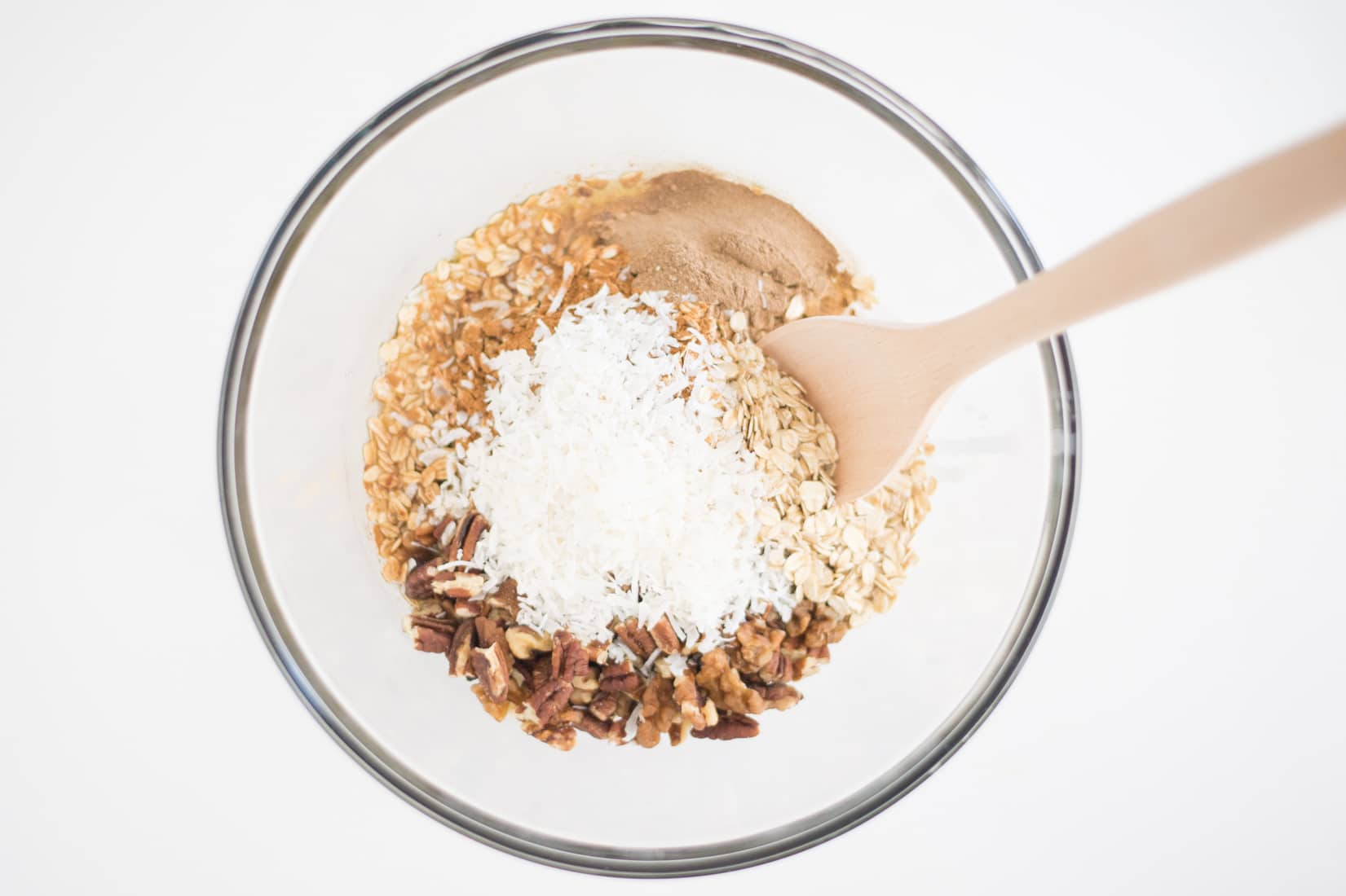 glass bowl full of oats, nuts, coconut oil, sugar, and chai spice with wooden spoon