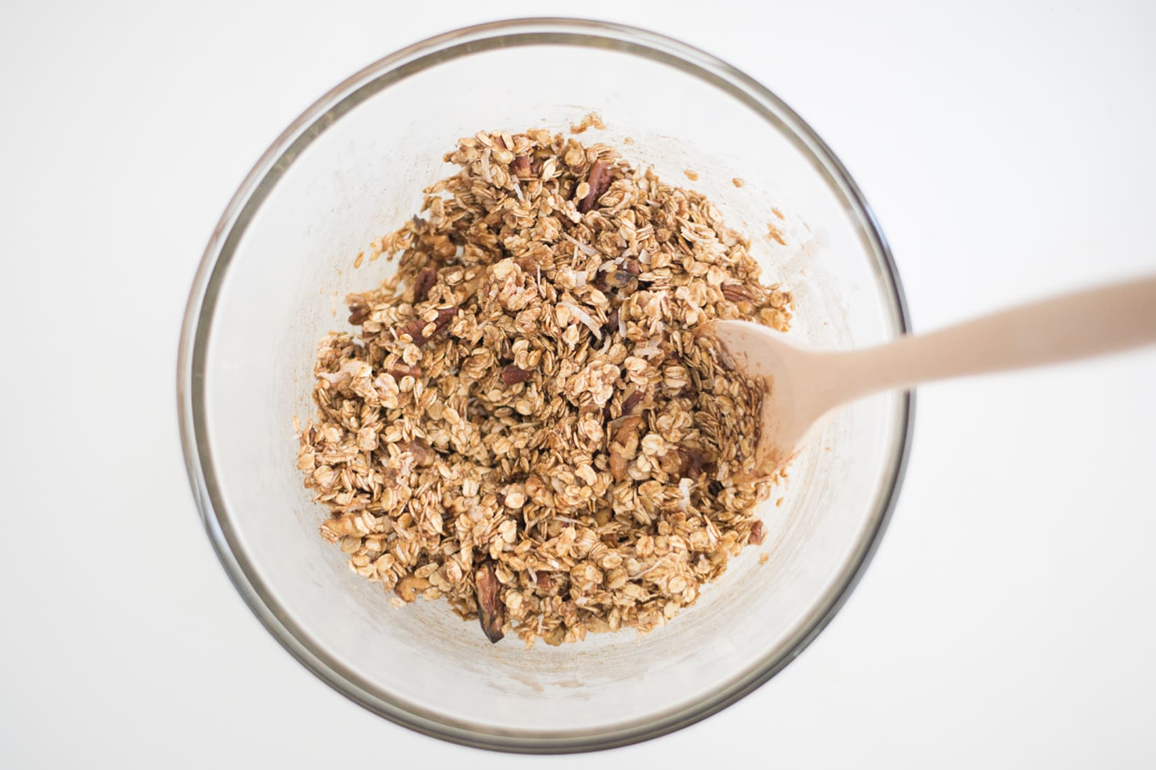 glass bowl full of oats, nuts, sugar, coconut oil, and chai spice with wooden spoon
