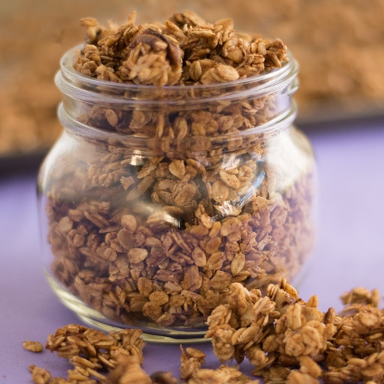 mason jar of vegan granola on purple background