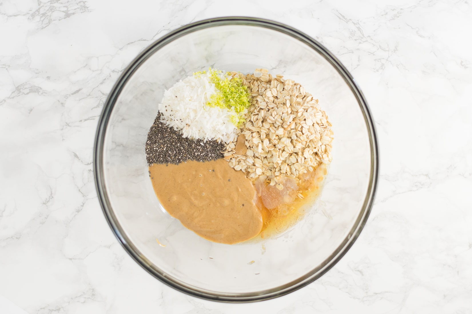 peanut butter, oats, chia seeds, coconut, lime zest, and agave in a mixing bowl on a marble counter