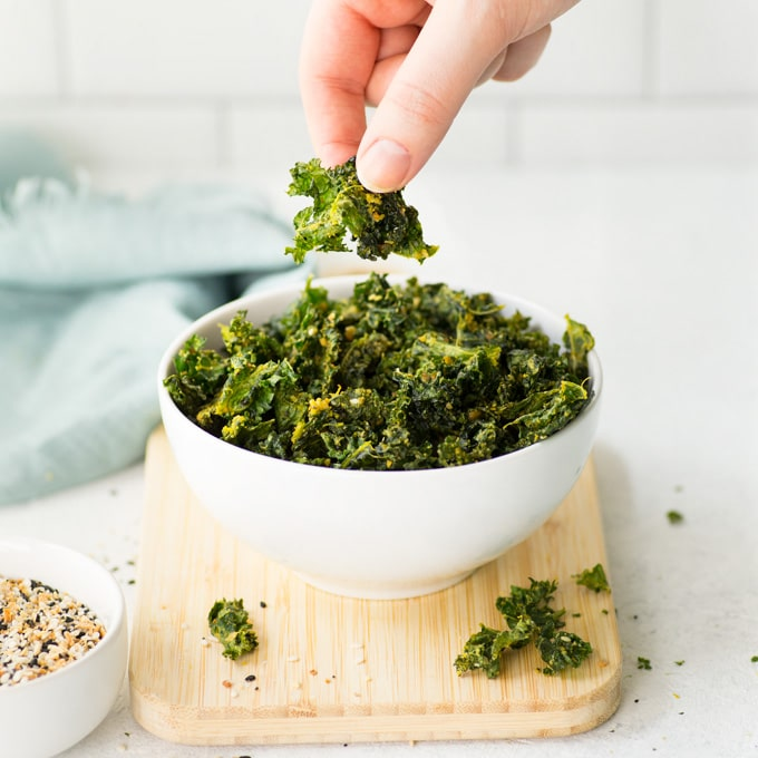 hand grabbing kale chip from white bowl