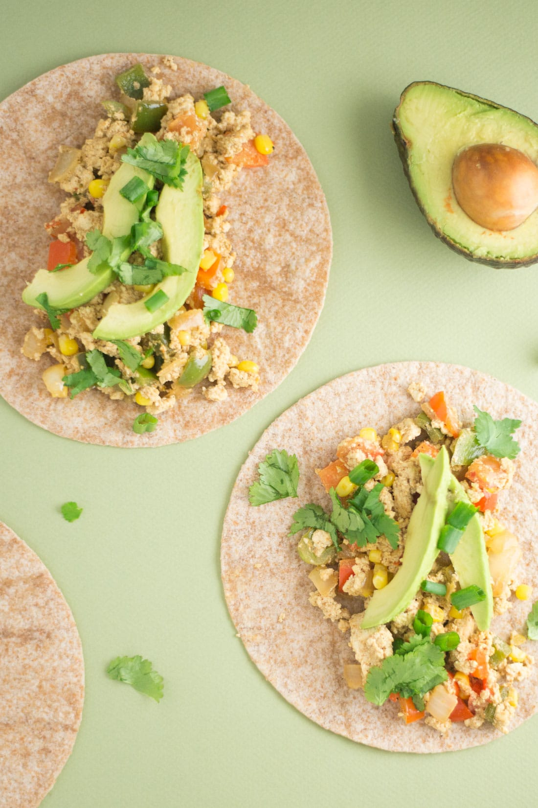 two vegan tacos with cilantro and avocado on green background