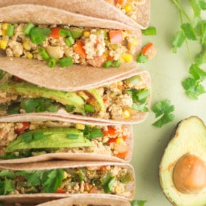 vegan tacos with avocado and cilantro on green background