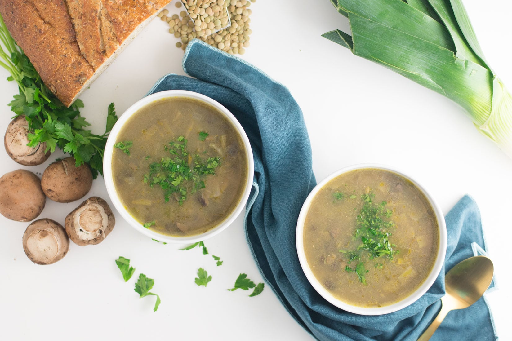 two bowls of vegan mushroom soup with bread, mushroom, leeks, and lentils