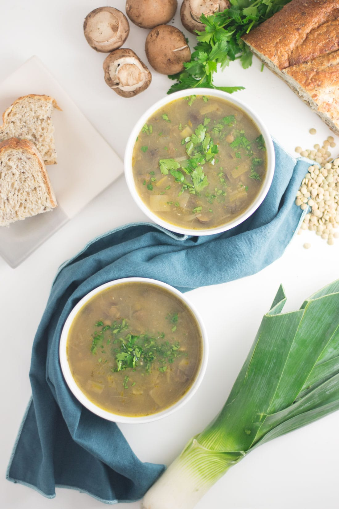 two bowls of vegan mushroom soup with bread, leeks, and mushrooms