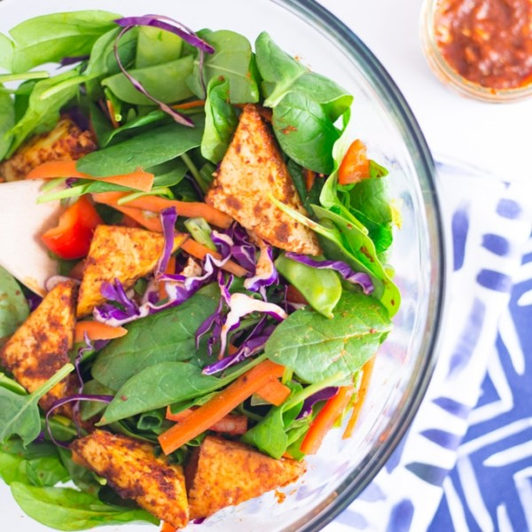 red thai curry tofu salad with spinach, carrots, and peppers