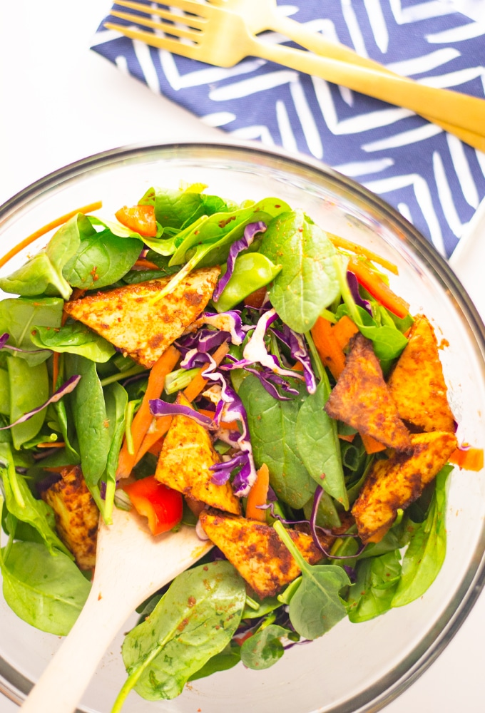 vegan red thai curry tofu salad with spinach, red cabbage, carrots, and snap peas