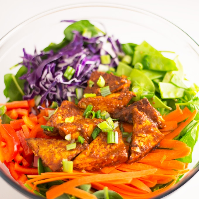 salad with spinach, carrots, pepper, cabbage, and red thai curry tofu