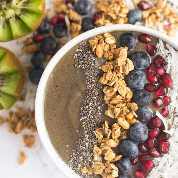 smoothie bowl topped with berries, chia seeds, coconut, and granola