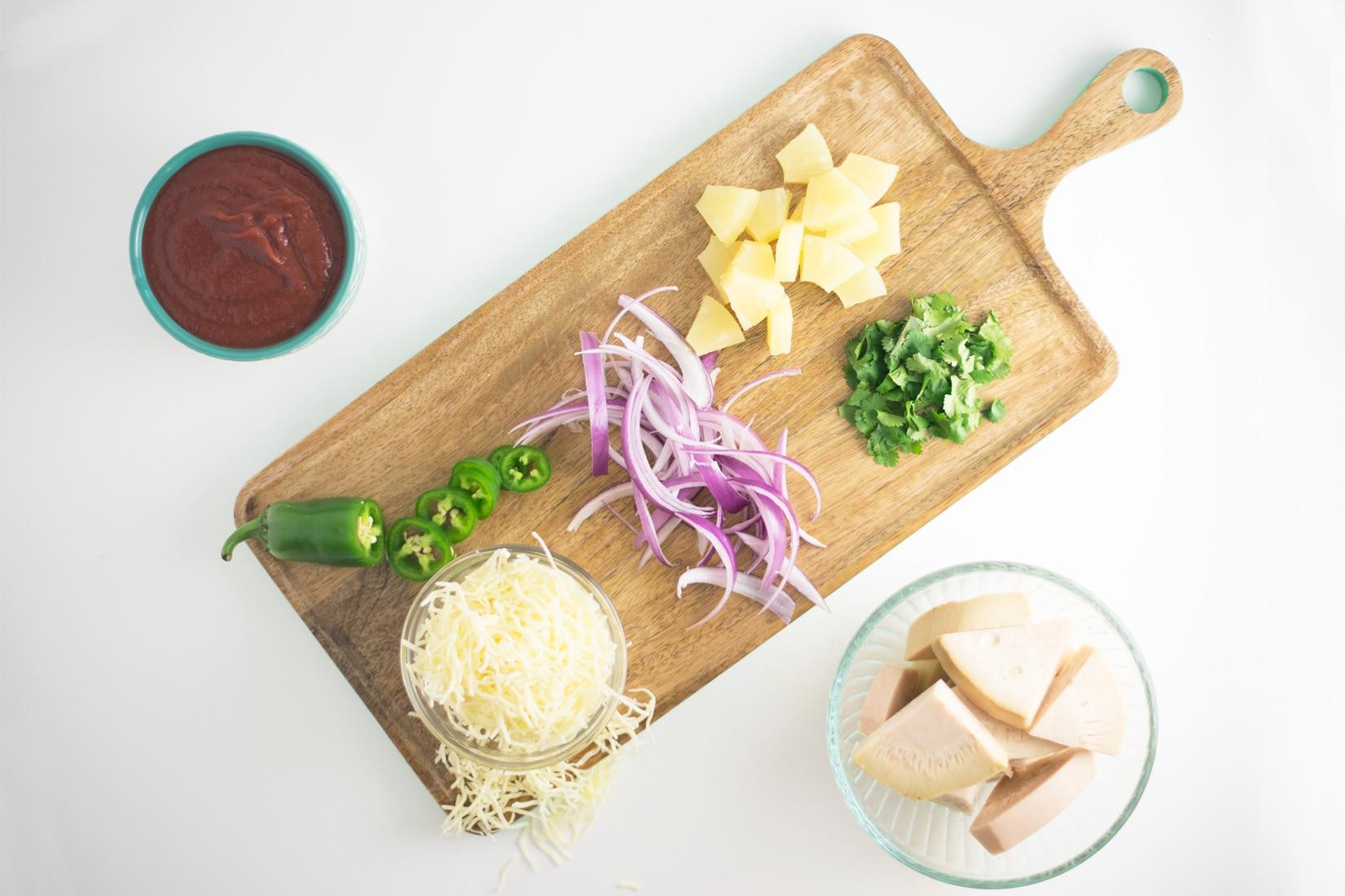 BBQ sauce, jackfruit, jalapenos, pineapple, red onion, cilantro on wooden board