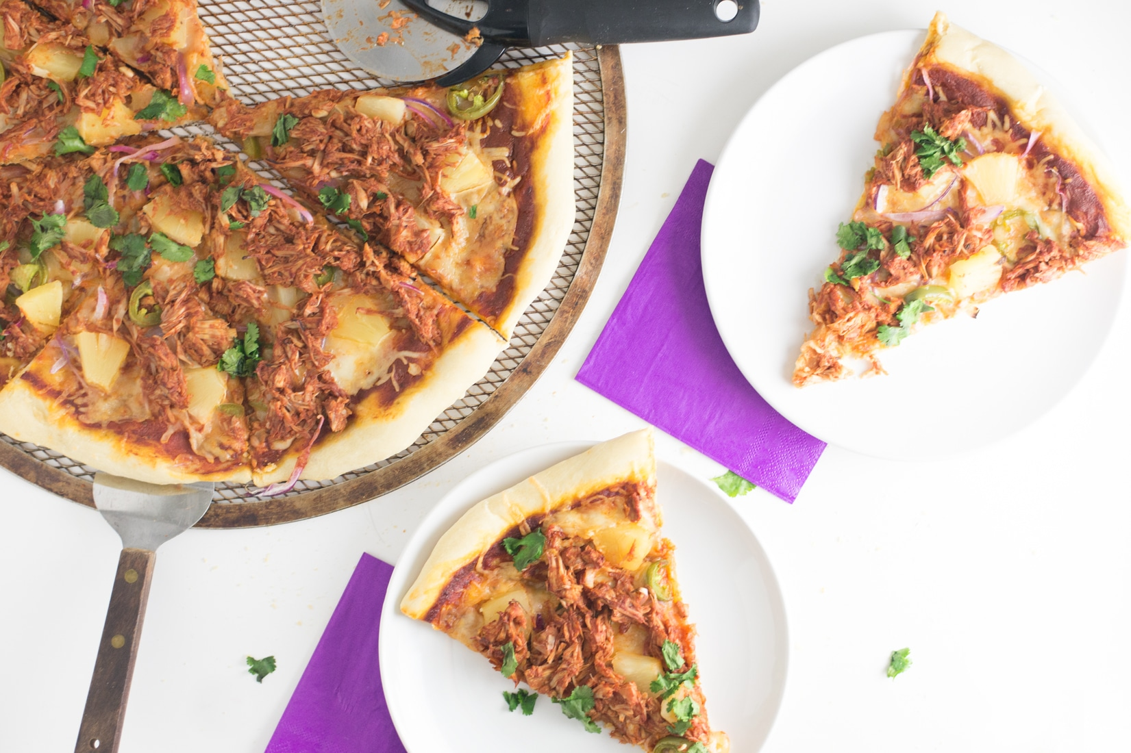 jackfruit pulled pork pizza with purple napkins and white plates
