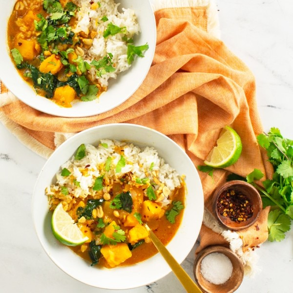 two bowls of vegan curry with lime, cilantro, chili flakes