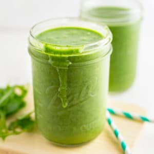 healthy mango green smoothie on wood board with teal straws
