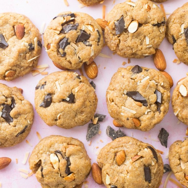 vegan chocolate chip cookies with almonds and coconut on pink background