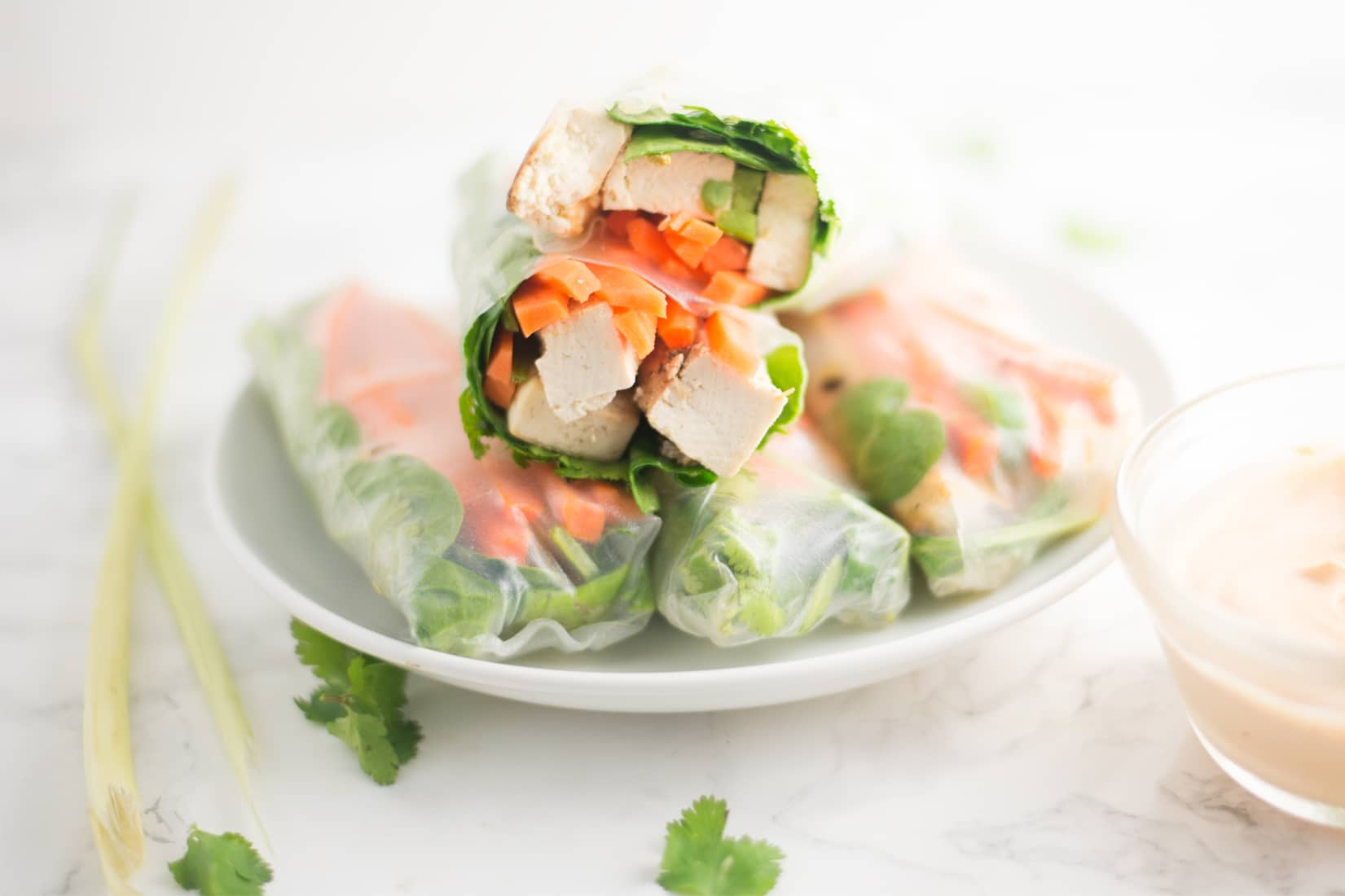 pile of spring rolls on white plate with cilantro, and lemongrass