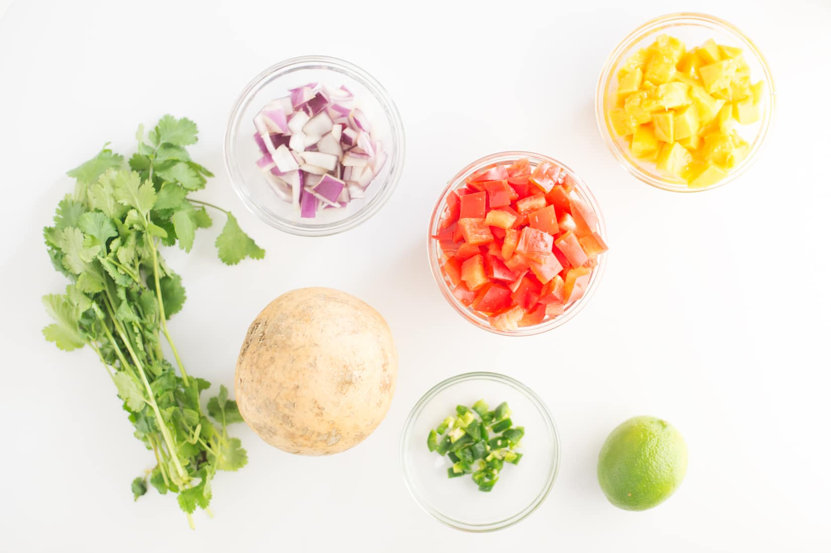 bunch of cilantro, diced red onion, diced red bell pepper, jicama, minced jalapeno, diced mango, and lime on white background.