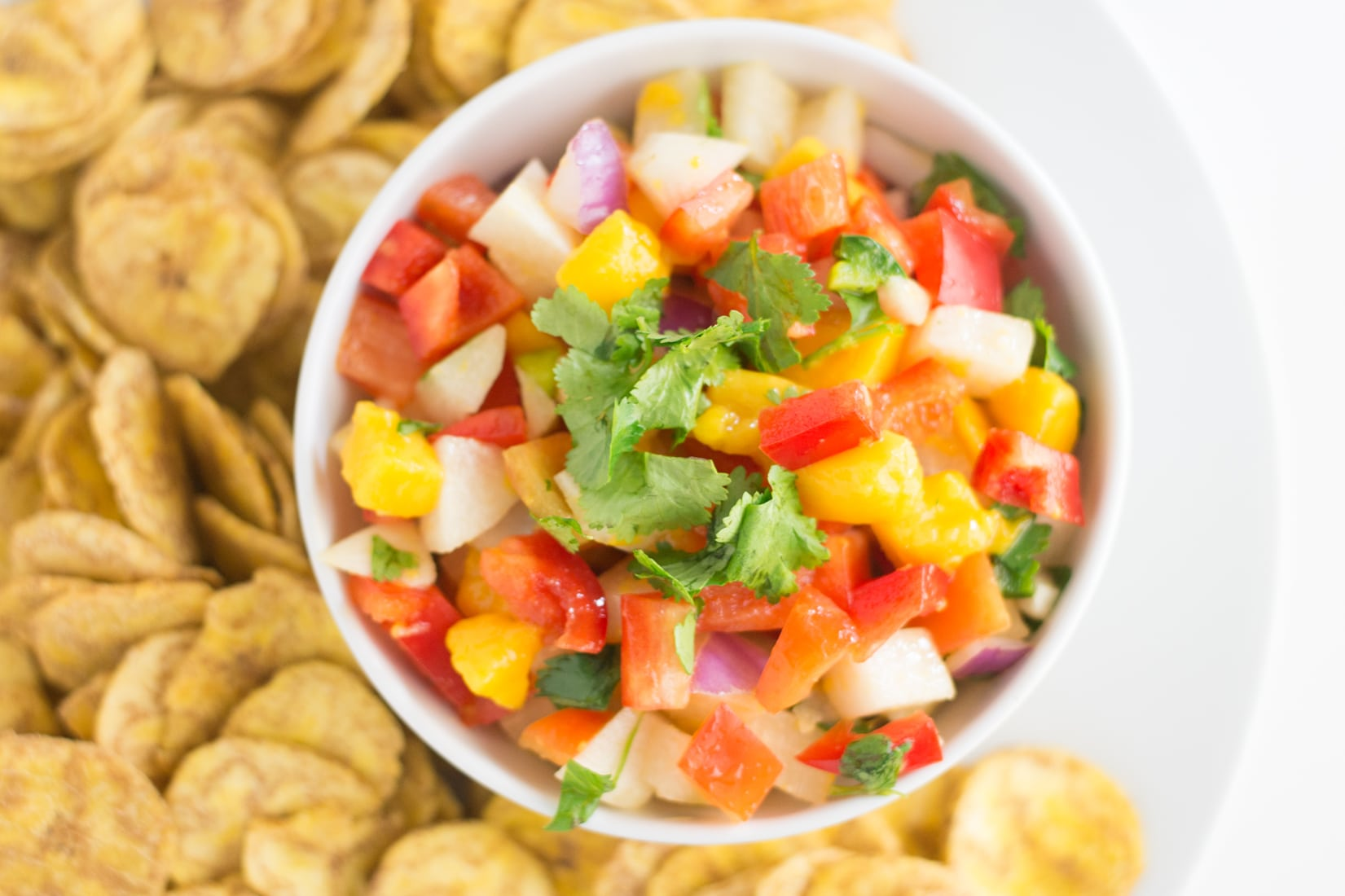 bowl of jicama mango salsa on a white plate with a pile of plantain chips