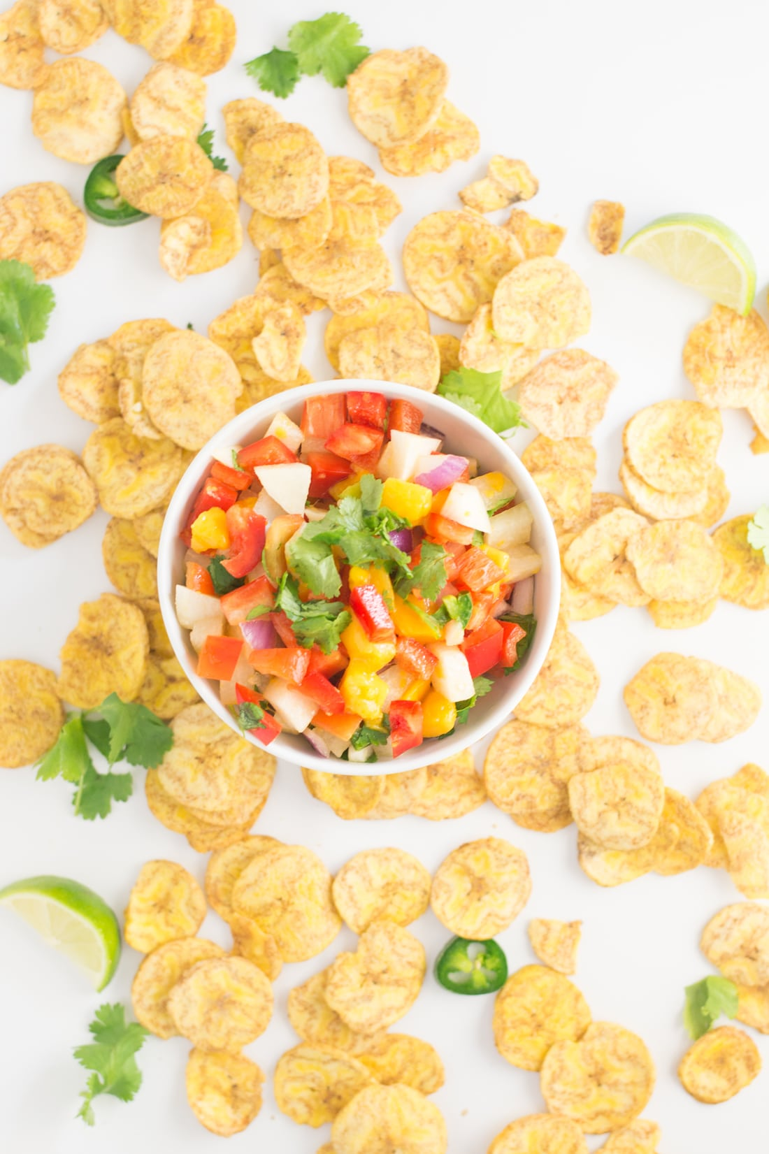 bowl of jicama salsa on white background with plantain chips and jalapenos.