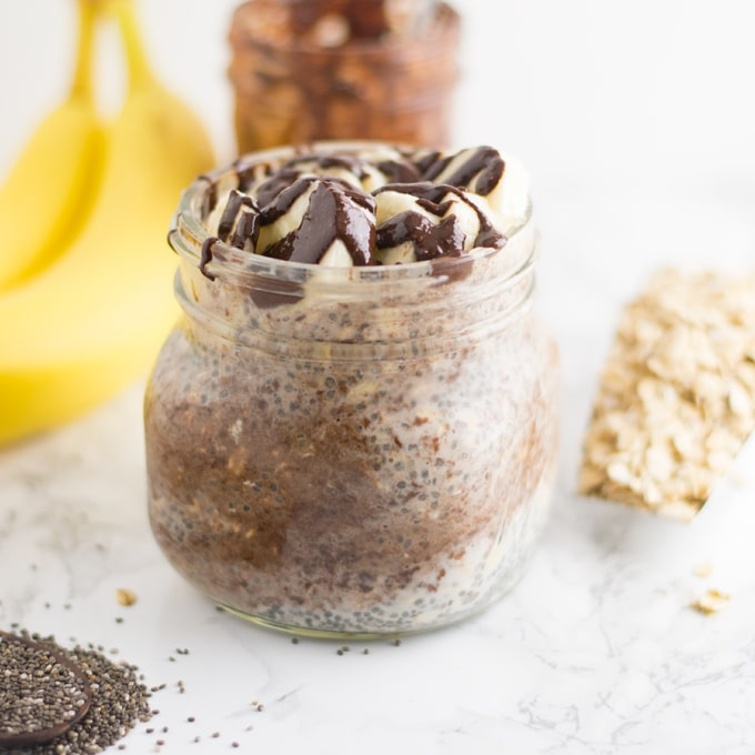 Overnight oatmeal with homemade vegan nutella, bananas on a marble background. Oats and chia seeds are in the background.