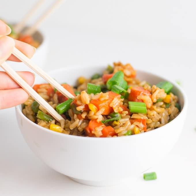 hand picking up vegan fried rice with chopsticks
