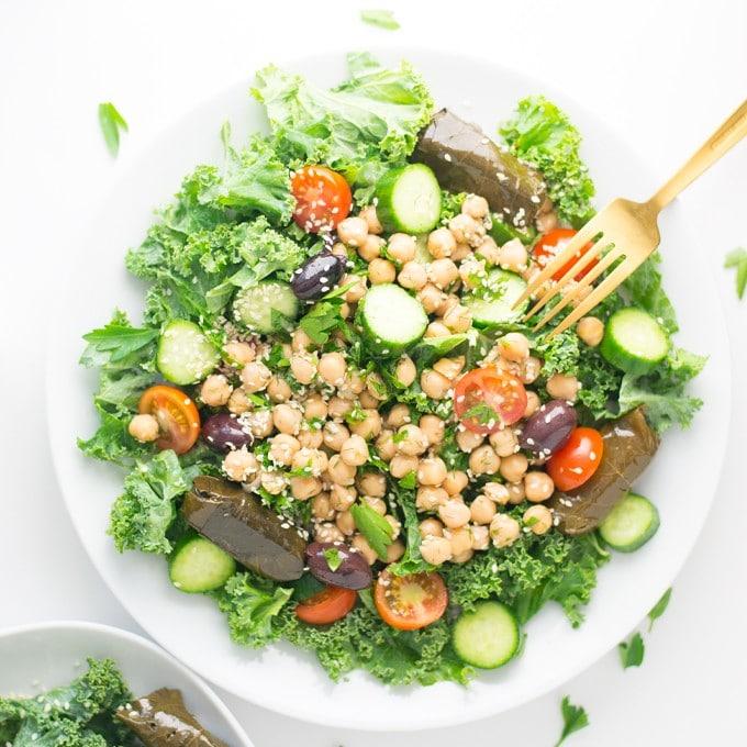 vegan greek salad with chickpeas, cucumbers, tomatoes, dolmas, hemp seeds, and tahini dressing
