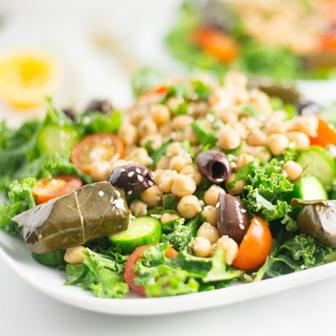 healthy vegan Greek salad with dolmas, chickpeas, olives, kale, tomatoes, and cucumber