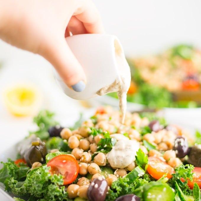 hand pouring homemade tahini dressing on vegan salad
