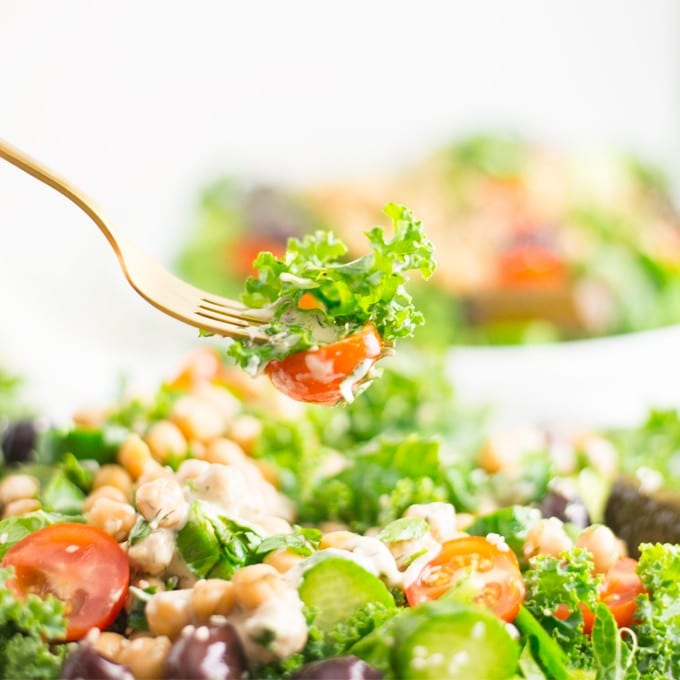 fork over salad with kale and tomato