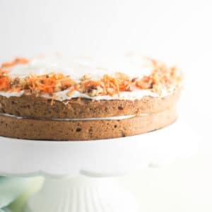vegan carrot cake on white cake stand