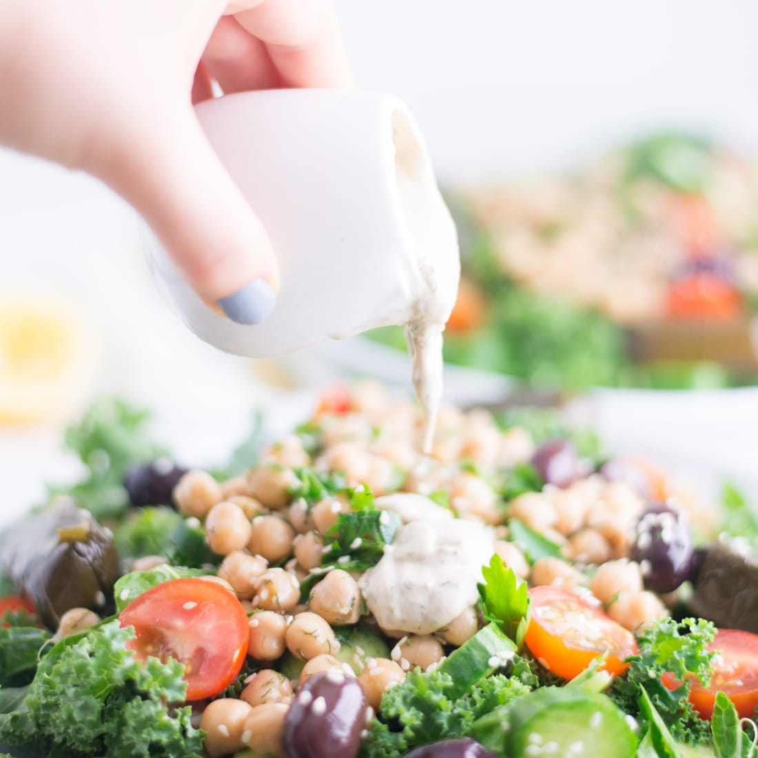 hand pouring dressing on vegan salad